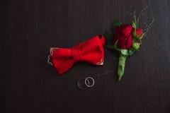 Accesorios de la boda del novio Boutonniere, anillos de oro y corbata de lazo rojos en fondo marrón Imágenes de archivo libres de regalías