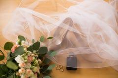 Accesorios de la boda El perfume negro, anillos de bodas, los zapatos beige de los bride's se cubre el velo Fotos de archivo
