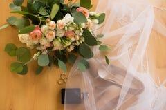 Accesorios de la boda El perfume negro, zapatos beige de los bride's, anillos de bodas, se cubre el velo Foto de archivo