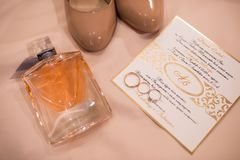 Accesorios de la boda: invitación, zapatos nupciales, anillos, perfume Detalles de la boda en sombras beige Fotografía de archivo libre de regalías