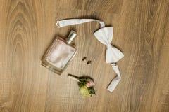 Accesorios de la boda Perfume rosado, pendientes nupciales con los diamantes, bowtie blanco y boutonniere con las pequeñas rosas Foto de archivo