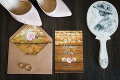 Accesorios de la boda que mienten en el fondo de madera: zapatos nupciales, anillos, invitación, espejos Detalles de la boda Visi Fotos de archivo