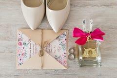 Accesorios de la boda: zapatos nupciales, anillos, invitación, perfume Detalles de la boda en sombras beige Imagen de archivo libre de regalías