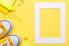 Accesorios de la escuela con el marco blanco en fondo amarillo Fotografía de archivo