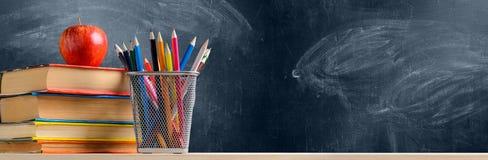 Accesorios de la escuela contra la pizarra Imágenes de archivo libres de regalías