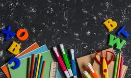 Accesorios de la escuela, efectos de escritorio en fondo oscuro Visión superior, espacio libre para el texto Foto de archivo
