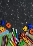 Accesorios de la escuela en un fondo oscuro Visión superior Fotografía de archivo libre de regalías