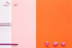 Accesorios de la escuela o de la oficina en fondo rosado y anaranjado foto de archivo