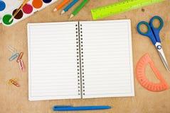 Accesorios de la escuela y cuaderno controlado en la madera fotos de archivo