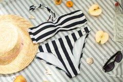 Accesorios de la mujer en la playa, el traje de baño, el sombrero y los vidrios foto de archivo