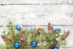 Accesorios de la Navidad en ramas del azul y del abeto en fondo de madera Imagen de archivo libre de regalías