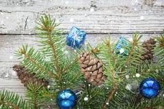 Accesorios de la Navidad en ramas del azul y del abeto en fondo de madera Imagen de archivo