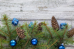 Accesorios de la Navidad en ramas del azul y del abeto en fondo de madera Imagenes de archivo