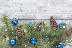 Accesorios de la Navidad en ramas del azul y del abeto en fondo de madera Foto de archivo libre de regalías