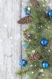 Accesorios de la Navidad en ramas del azul y del abeto en fondo de madera Foto de archivo
