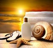 Accesorios de la playa con las toallas en la puesta del sol Fotos de archivo