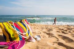 Accesorios de la playa de las mujeres en la orilla arenosa Imagen de archivo
