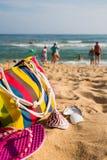 Accesorios de la playa de las mujeres en la orilla arenosa Imágenes de archivo libres de regalías
