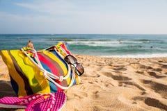 Accesorios de la playa de las mujeres en la orilla arenosa Imagenes de archivo