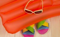 Accesorios de la playa del verano en el colchón de la natación Chancletas, gafas de sol Imagen de archivo libre de regalías
