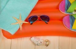 Accesorios de la playa del verano en el colchón de la natación Chancletas, gafas de sol, toalla Fotos de archivo libres de regalías