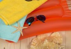 Accesorios de la playa del verano en el colchón de la natación Chancletas, gafas de sol, toalla Fotos de archivo