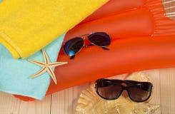 Accesorios de la playa del verano en el colchón de la natación Gafas de sol, toalla, conchas marinas Imágenes de archivo libres de regalías