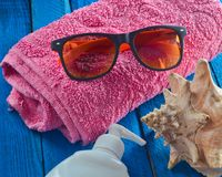 Accesorios de la playa del verano en una tabla de madera azul Toalla, gafas de sol, cáscara, sunblock El concepto de un centro tu Imagenes de archivo