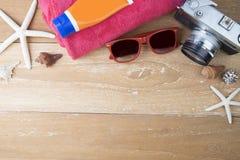 Accesorios de la playa del viaje del verano en el tablero de madera Imagen de archivo