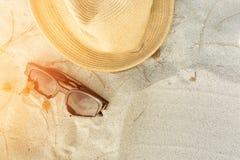 Accesorios de la playa en la arena con puesta del sol Foto de archivo libre de regalías