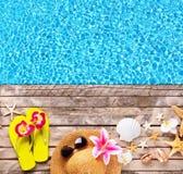 Accesorios de la playa en fondo de madera con la piscina Foto de archivo