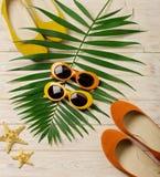 Accesorios de la playa - gafas de sol, sombrero y zapatos anaranjados y amarillos Foto de archivo