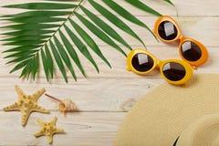 Accesorios de la playa - gafas de sol, sombrero y zapatos anaranjados y amarillos Imagen de archivo