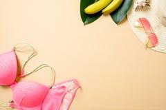 Accesorios de la playa de las mujeres: sombrero de paja, gafas de sol, traje de baño, plátano en fondo amarillo Concepto del viaj imágenes de archivo libres de regalías