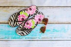 Accesorios de la playa Zapatos y toalla del verano con el fondo de madera de las gafas de sol Fotos de archivo libres de regalías