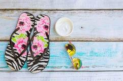 Accesorios de la playa Zapatos y toalla del verano con el fondo de madera de las gafas de sol Fotos de archivo