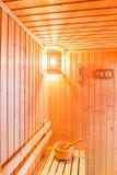 Accesorios de la sauna en el sitio de la sauna, lugar de madera del cubo en el banco Imagenes de archivo