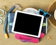 Accesorios de la tableta y de la playa en la arena Fotografía de archivo