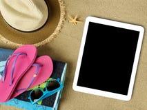 Accesorios de la tableta y de la playa en la arena Fotos de archivo libres de regalías