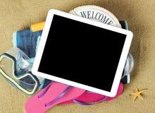 Accesorios de la tableta y de la playa en la arena Foto de archivo
