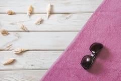Accesorios de la toalla y del verano de playa en el fondo de madera blanco concepto del recorrido Mofa en blanco para arriba para Imágenes de archivo libres de regalías