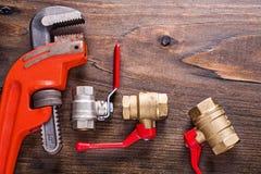 Accesorios de los fontaneros con las manijas y el mono rojos Fotografía de archivo libre de regalías