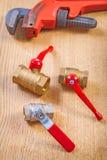 Accesorios de los fontaneros y llave inglesa en el tablero de madera Imagenes de archivo