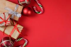 Accesorios de los presentes y de la Navidad en fondo rojo imagen de archivo libre de regalías