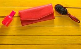 Accesorios de niña de la tendencia en un fondo de madera amarillo Cepillo para el pelo, monedero, botella de perfume Copie el esp Imagen de archivo