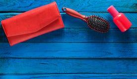 Accesorios de niña de la tendencia en un fondo de madera azul Cepillo para el pelo, monedero, botella de perfume Copie el espacio Fotos de archivo