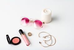 Accesorios decorativos vela y gafas de sol de los cosméticos sobre el fondo blanco Imagen de archivo