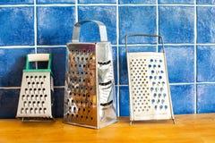 Accesorios del artículos de cocina ralladores del acero inoxidable en el tablero de madera Fondo embaldosado azul Imagen de archivo