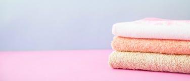 Accesorios del baño - las toallas doblaron, apilado en una luz, un fondo azul y rosado brillante el concepto de cuidar para sí mi Foto de archivo