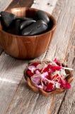 Accesorios del balneario: piedras calientes para el masaje y las flores Foto de archivo